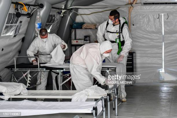 A view taken on March 20 2020 in Cremona southeast of Milan shows cleaning personnel in protective gear disinfecting patients' beds in one of the...