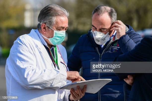 A view taken on March 20 2020 in Cremona southeast of Milan shows Healthcare Director of the Cremona hospital Rosario Canino talking with a person at...
