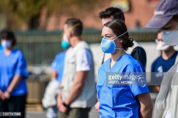 View taken on March 20, 2020 in Cremona, southeast of Milan, shows volunteers looking on during the opening of a newly operative field hospital for...