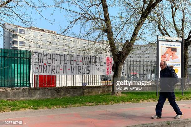 """View taken on March 20, 2020 outside the hospital of Cremona, southeast of Milan, shows a man walking past a banner reading """"fight and win against..."""