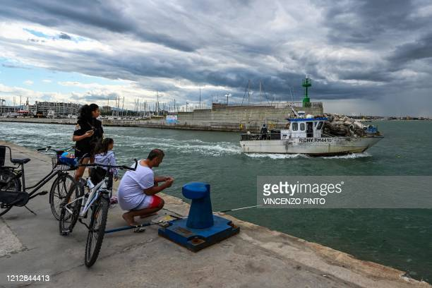 A view taken on May 11 2020 shows a fisherman and his family watch a fishing boat leave the port of Rimini on the Adriatic coast northeastern Italy...