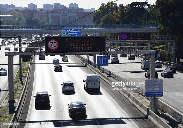 A view taken on November 13 2015 shows vehicles on the M30 speedway as roadsings read speed limitation due to a peak of pollution in Madrid Madrid...