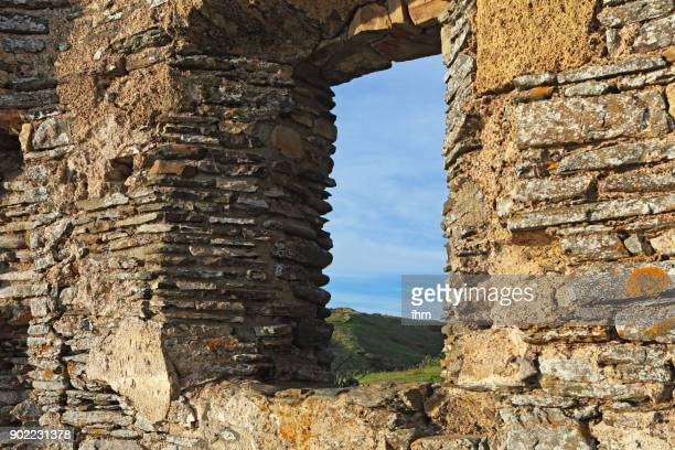 A View thorugh the window of the ruin of a historic church in the french Normandy, arneville-Carteret, France