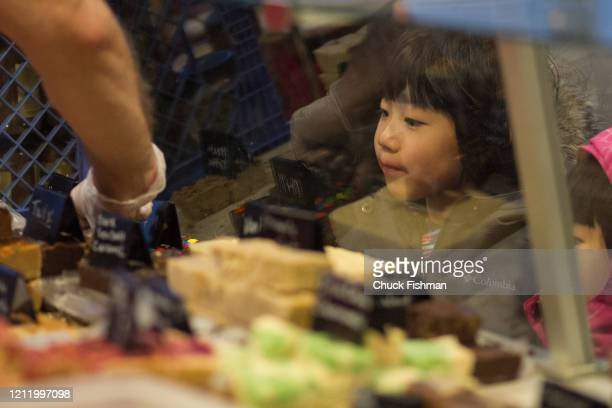 View though a display case as a young girl looks at varieties of fudge on display at the Chocolate Expo held in the Cradle of Aviation Museum Garden...