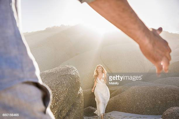 View though mans arms of woman wearing white dress running to him