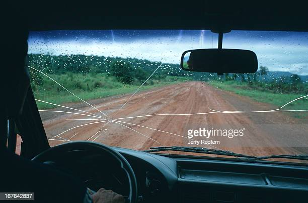 A view through a cracked taxi windscreen on the lonely road between Koh Kong and Sre Ambel in Cambodia For years this road essentially did not exist...
