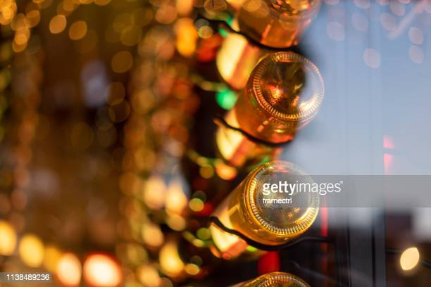 view through a restaurant window with defocused background and bottles of restaurant, bar, winery or cafeteria. - celebration fl stock pictures, royalty-free photos & images