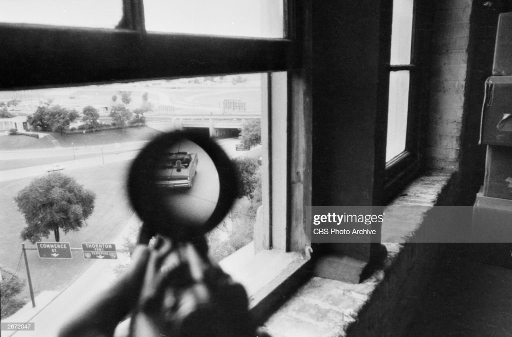 A view through a rifle scope aimed from the window of the Texas Schoolbook Depository shows a convertible car during a Warren Report story, Dallas, Texas, June 10-11, 1967. The Warren Report was an investigation of the John F. Kennedy assassination.
