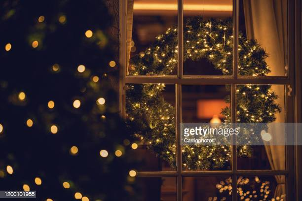 view through a window of a christmas wreath in a living room - christmas stock pictures, royalty-free photos & images