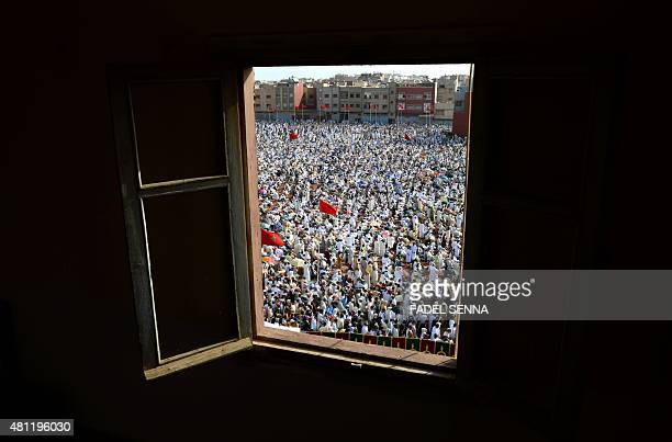 A view through a window shows Moroccan Muslims performing prayers for Eid alFitr which marks the end of the Muslim holy fasting month of Ramadan in...