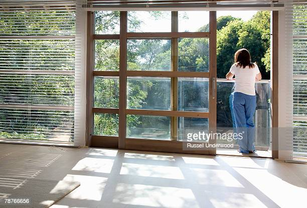 view through an empty room of a woman standing on a balcony - tracksuit bottoms stock pictures, royalty-free photos & images