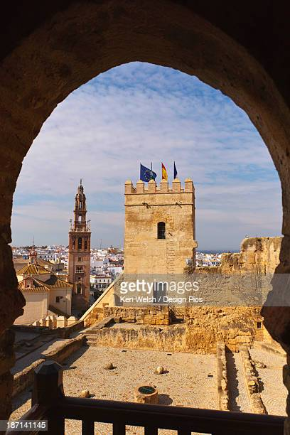 view through arabic horseshoe shaped arch across patio of the cisterns to the keep of the alcazar with church of san pedro behind - carmona fotografías e imágenes de stock