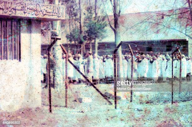 View through barbed wire fencing of a group of men dressed in white robes and headbands standing with fists raised in a large courtyard in Iran March...