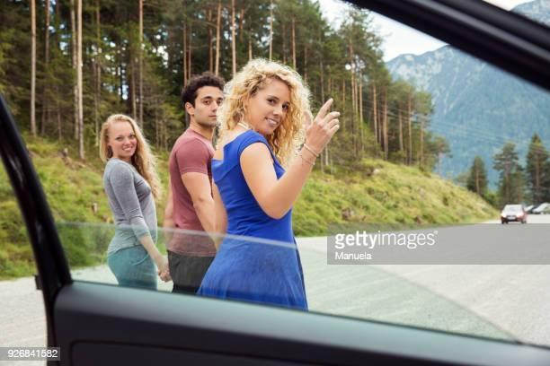 View through car window of friends looking over shoulder at camera, Innsbruck, Tirol, Austria, Europe