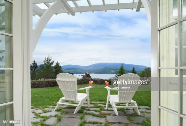 view through doors to adirondack chairs, lake and mountains - moosehead lake stock photos and pictures