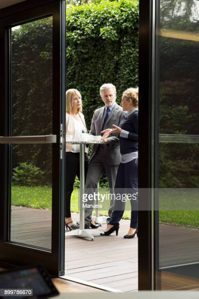 View through doorway of colleagues standing at patio table enjoying refreshments