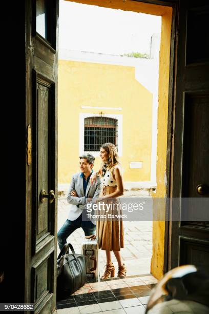 View through doorway of hotel of smiling couple waiting with luggage for car service