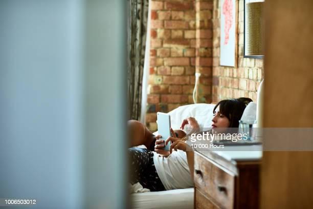 view through doorway towards woman reading in bed - pessoas serenas imagens e fotografias de stock