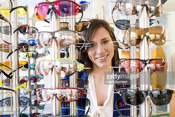 view through eyeglasses display of woman looking at camera smiling - sigrid gombert stock-fotos und bilder