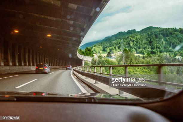 view through front window of car, driving on a freeway in a anti-avalanche-tunnel - dashboard camera point of view stock photos and pictures