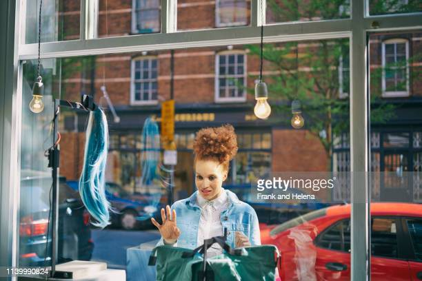 view through glass of young woman looking in shop window - helena price stock pictures, royalty-free photos & images