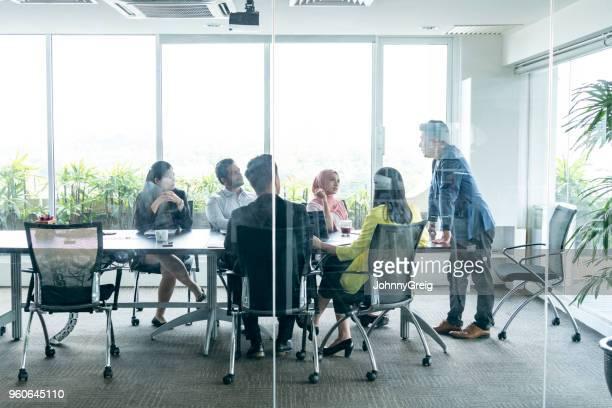 kijk door het glas naar zakelijke bijeenkomst - zakenbijeenkomst stockfoto's en -beelden