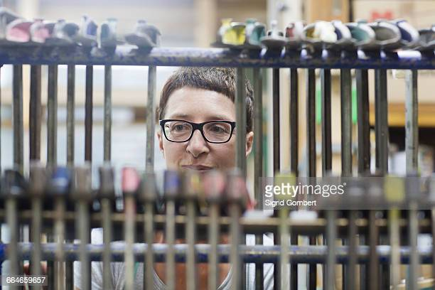 view through hanging clamp tools of woman in workshop - sigrid gombert photos et images de collection