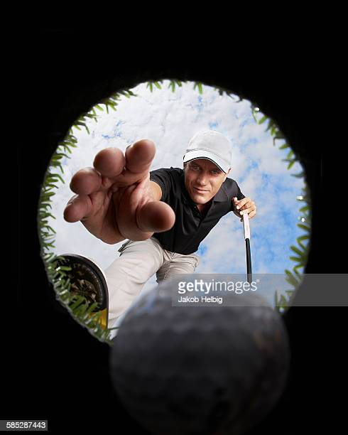 view through hole of golfer reaching for golf ball - hole stock photos and pictures