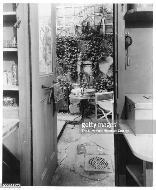 View through kitchen doorway of small table at the home of artists George Mary Stonehill chair in garden trellis and climbing vines behind New York...
