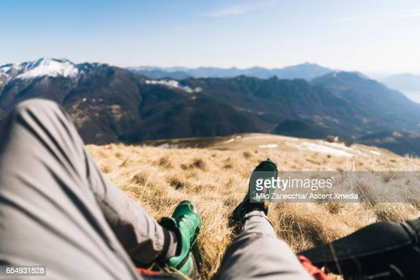 View through legs of hiker relaxing on mountain summit