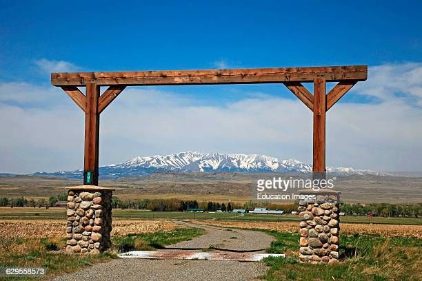 View through Montana ranch entrance to rangeland with a view of central Montana's snow covered Crazy Mountains in the background The Crazy Mountains...