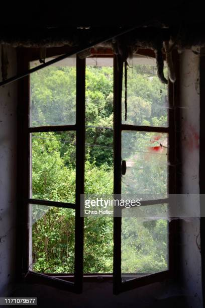view through old window with broken window panes - image photos et images de collection