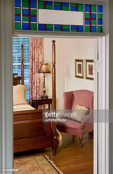 View through open door to armchair next to double bed