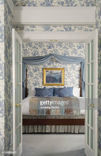 View through open double doors to bed with blue curtains above