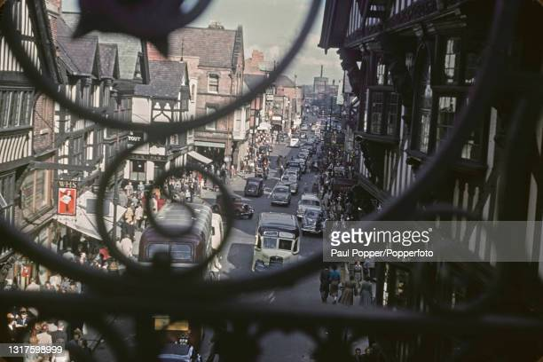 View through railings of cars, buses and pedestrians making their way along a main street in the Rows area of Chester in Cheshire, England circa 1960.
