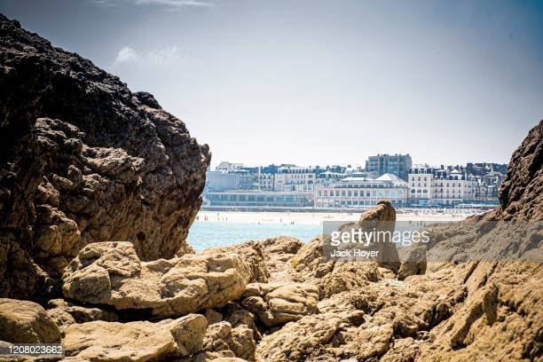 view through rocks to the beach of dinard - dinard stock pictures, royalty-free photos & images