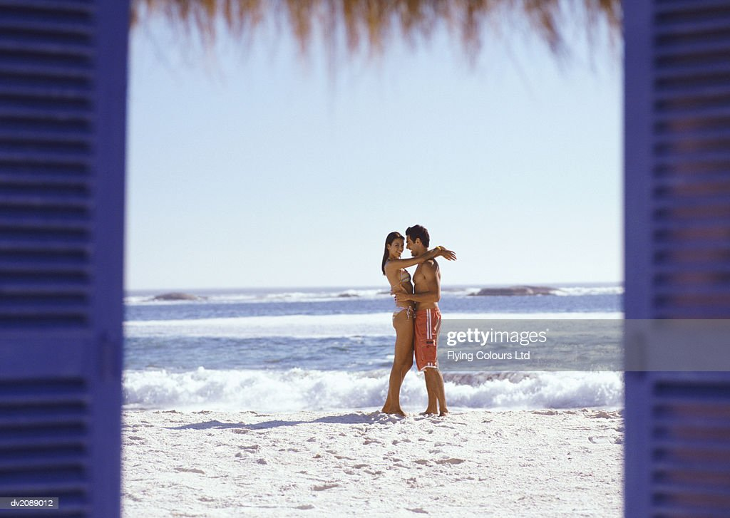 View Through Shutters of a Couple Standing on a Beach by the Water's Edge, Embracing : Stock Photo