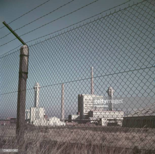 View through the security fence of the Magnox reactors reprocessing plant and pile chimneys at the Windscale nuclear power generating site in...