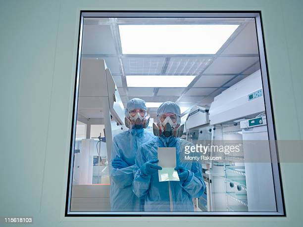 View through window at scientists in full protective clothing and masks, in clean room of laboratory
