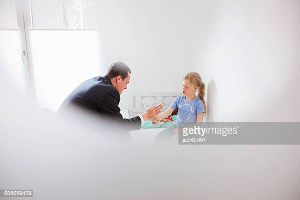 view through window of father playing hand clapping game - slapping stock pictures, royalty-free photos & images