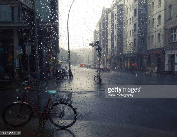 view through window of rain in the streets of berlin, germany - wetter stock-fotos und bilder