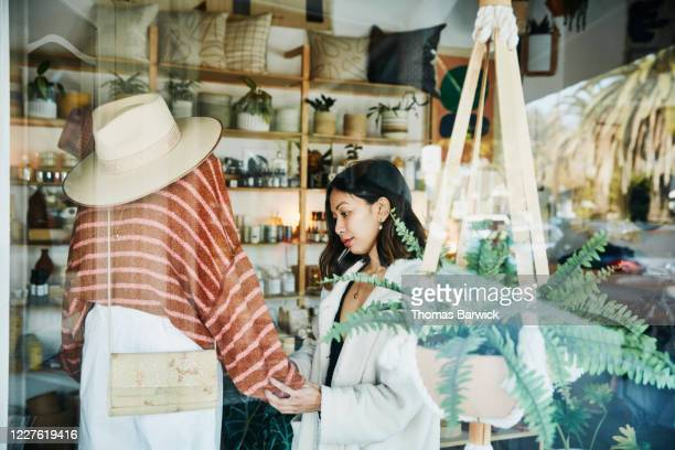 view through window of shop owner adjusting mannequin in clothing boutique - small business stock pictures, royalty-free photos & images