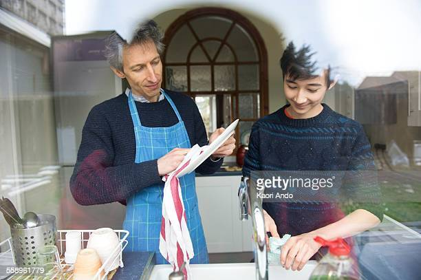 View through window of teenage boy and father washing up in kitchen