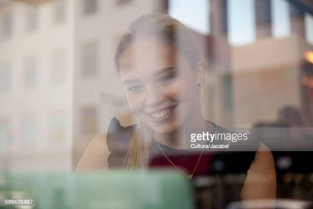 View through window of teenage girl using laptop computer looking down smiling, Reykjavik, Iceland