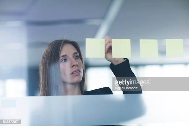 view through window of young woman writing on post it note stuck to glass - sigrid gombert stock-fotos und bilder