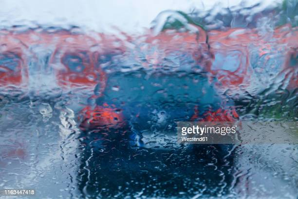 view through windscreen on rainy evening while waiting at level crossing - moving past stock pictures, royalty-free photos & images