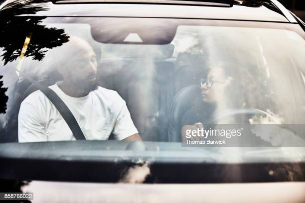 View through windshield of car of father teaching daughter to drive