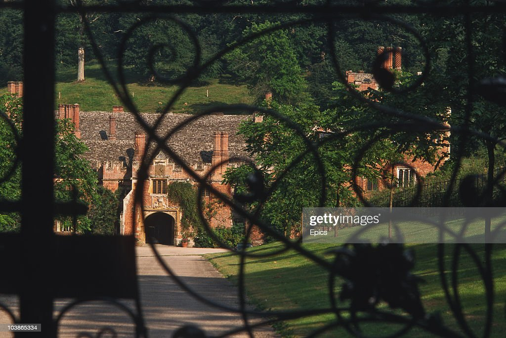 A view through wrought iron gates of Compton Wynyates, a Tudor period country manor house, Warwickshire, August 1997. King Henry VIII stayed multiple times at Compton Wynyates, and his bedroom window still retains the king's arms in stained glass.