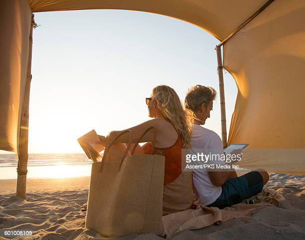 View thru beach canopy to couple with book, tablet