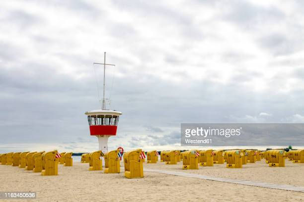 View to beach with hooded beach chairs and attendant's tower, Luebeck Travemuende, Germany